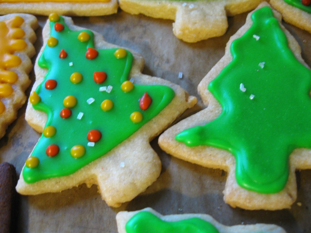 Sugar cookies shaped like trees with green frosting and decorations of red and yellow ornaments.
